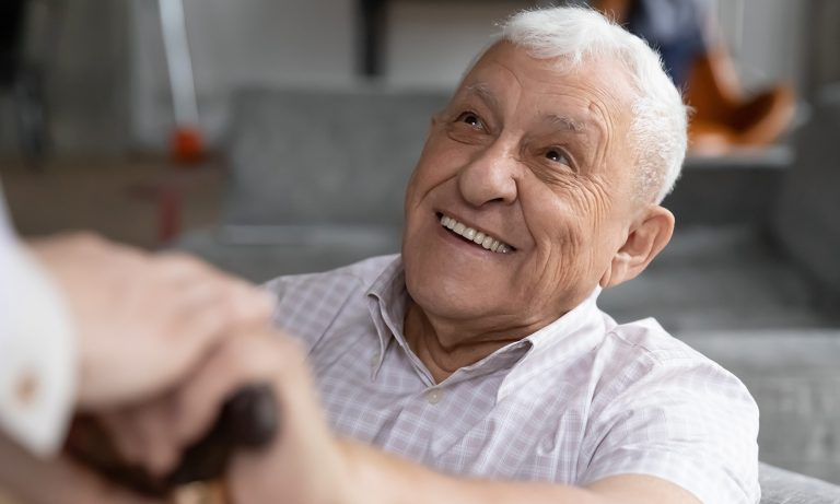 Old man sitting, smiling at person whose hand rests on his as he grips the handle of his cane