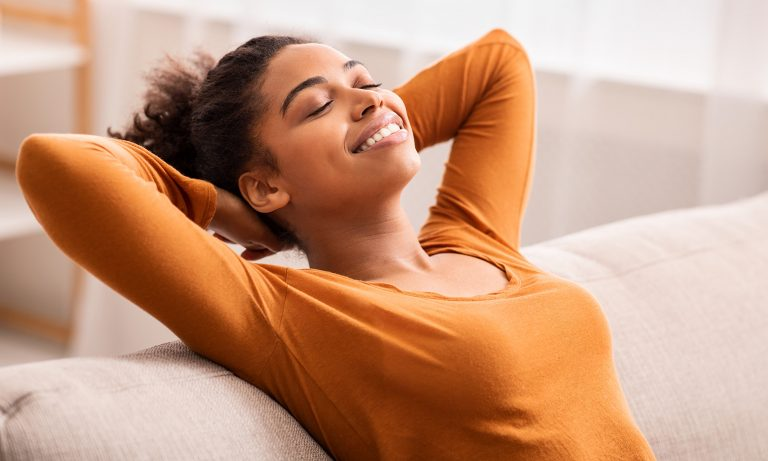 Smiling young woman on couch, hands clasped behind her head, leans back