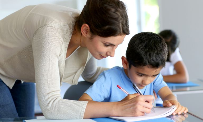 Teacher leaning over shoulder of young boy at his classroom desk, guiding him by marking with her pencil on his notebook