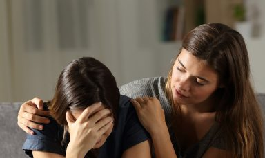 Teen girl comforting sad friend beside her on couch
