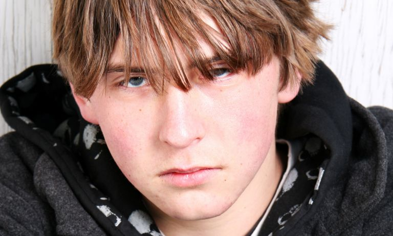 Closeup of teenaged boy appearing zoned out, his face devoid of affect