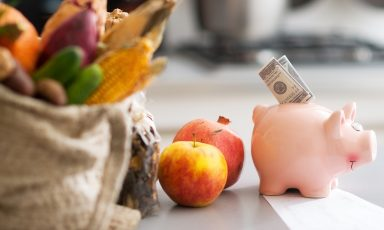 Piggy bank with folded cash bill nestled in slot, in front of bagged produce, pomegranate, and apple, frugal budget food shopping