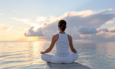 Woman at edge of dock, sitting in lotus position
