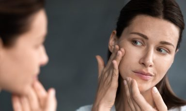 Woman examining face in mirror unhappy