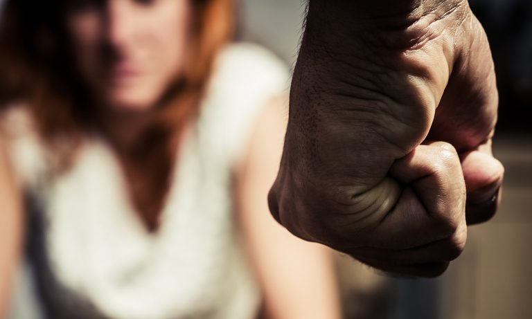Man's clenched fist viewed from behind, woman cowering in front of him