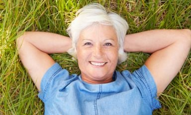 Senior woman lying on grass, resting her head on her hands, relaxing, smiling towards us