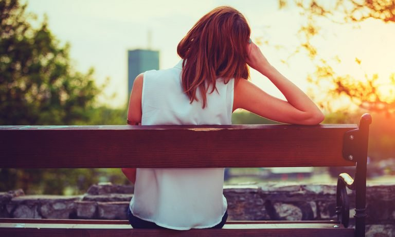 View from behind of woman sitting on park bench