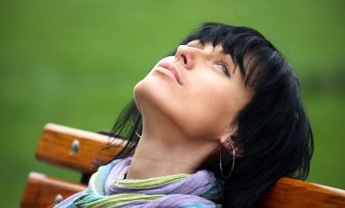 Closeup of woman sitting on park bench, head leaning back against backrest, lost in thought