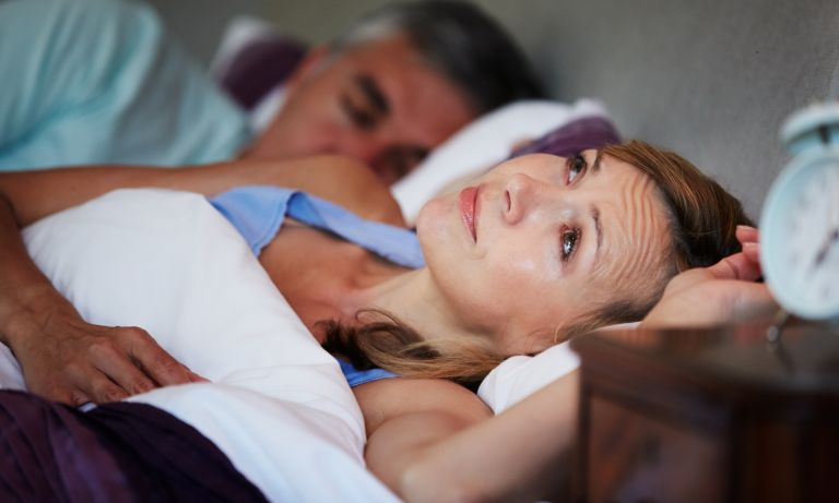 Woman lying in bed next to partner, face up, eyes open, unable to sleep