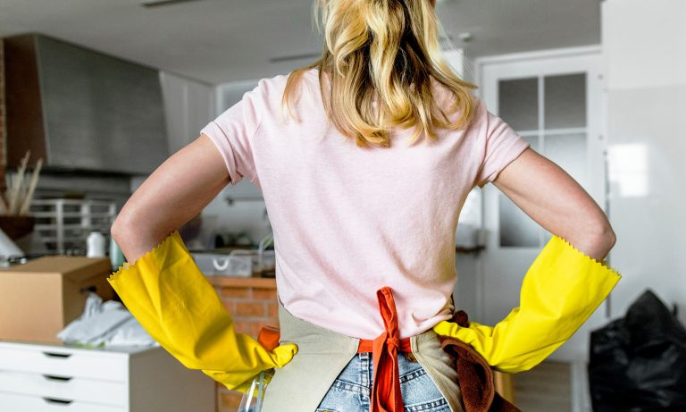 View from behind of woman staring at messy house, apron and cleaning gloves on, hands on hips