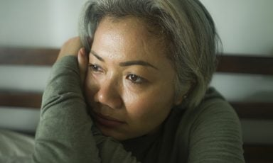 Sad-looking woman with arms folded, pressing cheek against her hand