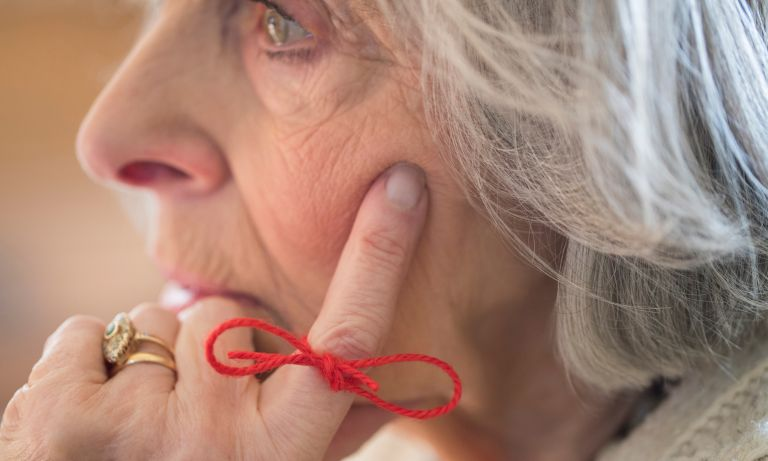 Elderly woman, hand on side of face, reminder string tied in bow on finger