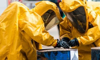 Two people in hazmat gear work together, focusing their efforts near the top rim of a rusty, warped, chemical filled drum