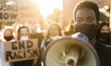 Young black man, at head of protest group, holds megaphone to his mouth