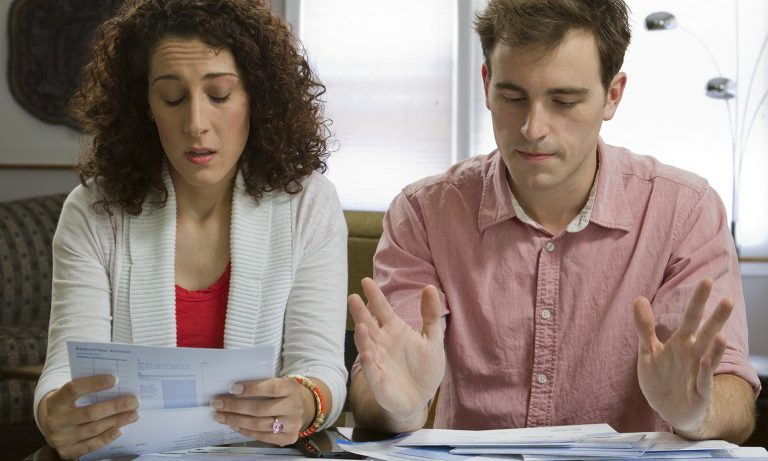 Young couple at table at home reviewing their personal financials, woman concerned, man fed up