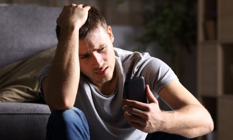 Young distraught man sitting on floor in front of bed, elbow on knee, hand on scalp, looking at phone in his other hand
