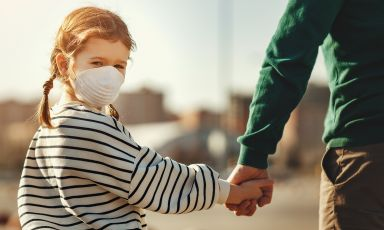 Young girl wearing protective mask looks back towards us as she holds am adult relative's hand during an outdoor activity