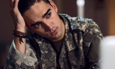 Young man wearing army fatigue jacket, leaning elbow on table, head tilted to rest against palm of his hand, his gaze distant