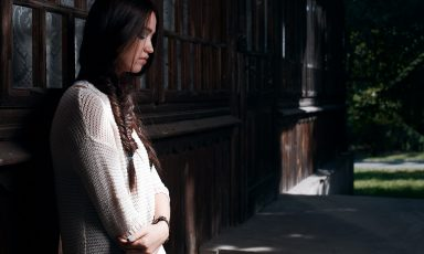 Young woman, gently leaning against exterior wall, illuminated by shaft of sunlight, eyes closed with reflective thoughts
