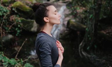 Young female yoga practitioner, hands overlapped over chest, engages in Pranayama breathing exercise outside, a waterfall behind
