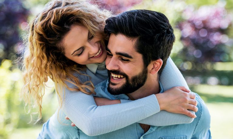 Young woman hugging partner from behind while getting piggy back ride