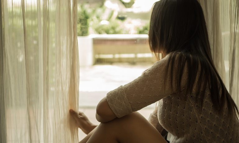 Sad woman holding the curtains open to look out of a large light window at home