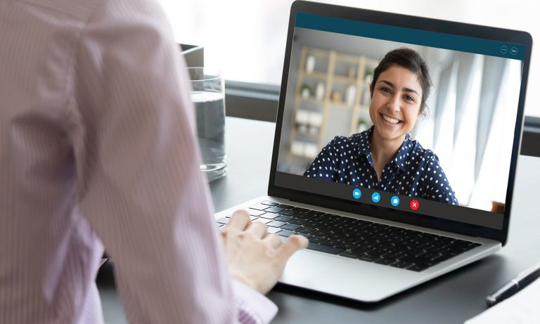 Young woman smiling in video call window on laptop display
